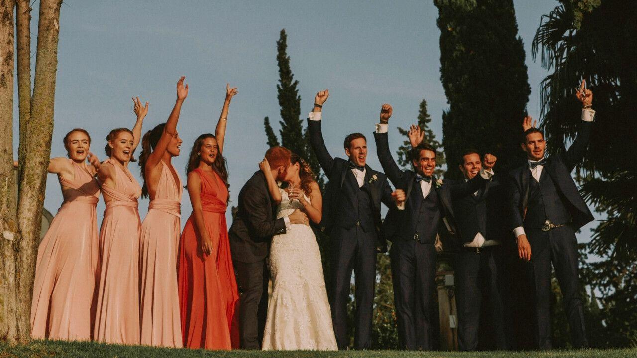 La coppia insieme alle damigelle e i tesmoni dello sposo mentre festeggiano tutti insieme, alzando le braccia al cielo mentre la coppia si bacia