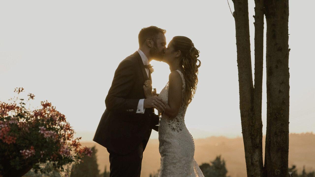 Un tenero bacio tra John e Marianna sotto il sole dorato della Toscana al tramonto, alla Antica Fattoria di Paterno.