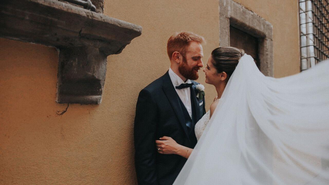 La coppia è appoggiata ad una parete degli edifici nelle strade di Lucca