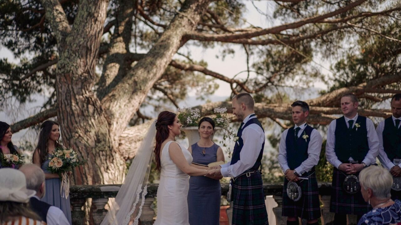 Kathryn and Ross hold each other hands, Carina - the wedding officiant - is reading their love stories.