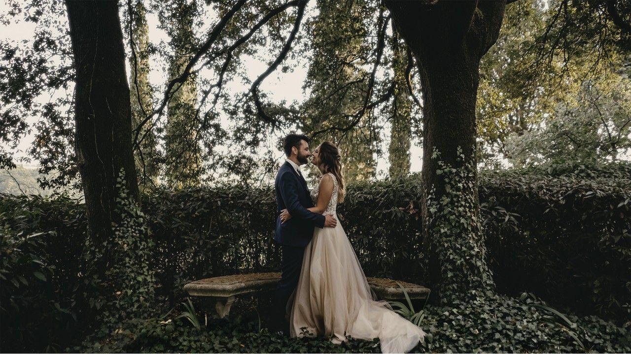La coppia di sposi si abbracciano tra gli alberi del giardino segreto di Villa Dianella.