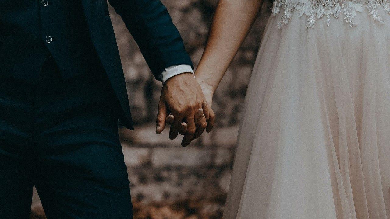 Dettaglio della coppia di sposi che si tiene per mano.